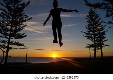 Silhouette of a young woman jumping on a slackline in the open air between two trees at sunset at scarborough beach in Perth, Australia.
