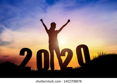 Silhouette of young woman jumping on the hill with 2020 happy new years. Conceptual image of freedom and successful in New year.