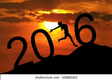 Silhouette young woman jumping on the hill and forming numbers 2016 while celebrating new year