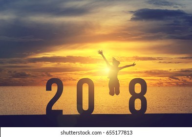 Silhouette young woman jumping on the sea and 2018 years while celebrating new year, happy victory and success concept.