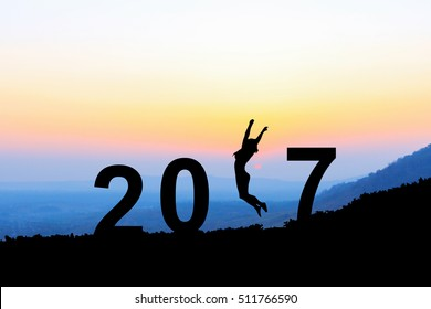 Silhouette young woman jumping over 2017 years on the hill at sunset, while celebrating new year.