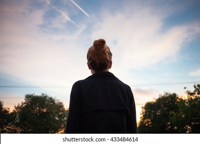 The silhouette of a young woman looking at sunset in the distance.