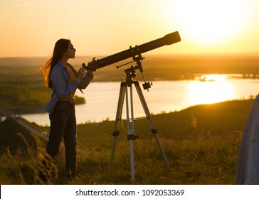 Silhouette of young woman looking view through the telescope at summer sunset