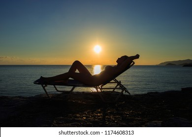 Silhouette of the young woman is lying on the deckchair at sunset.
