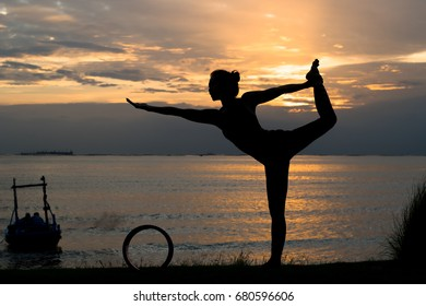 The silhouette of a young woman meditating by yoga at the seafront in the pre-sunset time, this activity makes you feel calm. Healthy body, health and good mental health