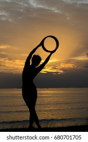 The silhouette of a young woman meditating by yoga at the seafront in the pre-sunset time, this activity makes you feel calm. Healthy body, health and good mental health.