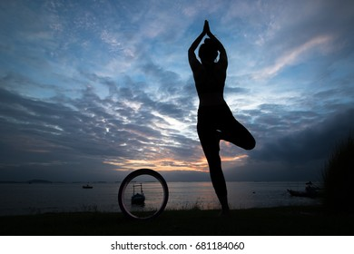 The silhouette of a young woman meditating by yoga wheel at the seafront in the pre-sunset time, this activity makes you feel calm. Healthy body, health and good mental health