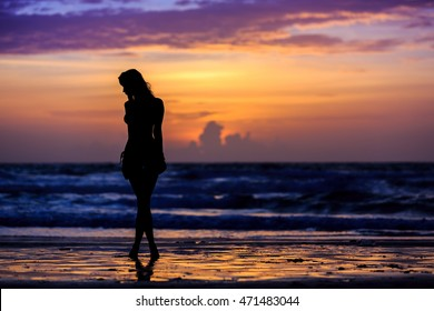 Silhouette young woman on the beach at sunset / Silhouette young woman