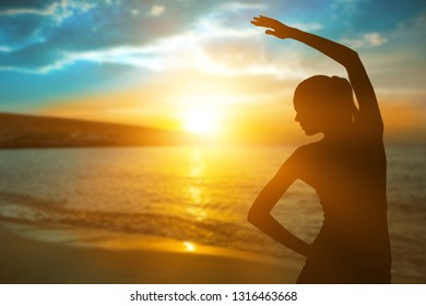 Silhouette of young woman on sea coast in sunset