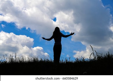 Silhouette young woman open arms on hill