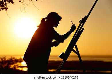 silhouette of a young woman painting a picture with paints on canvas on an easel outdoors, girl with paint brush and palette engaged in art on the nature in a field at sunset