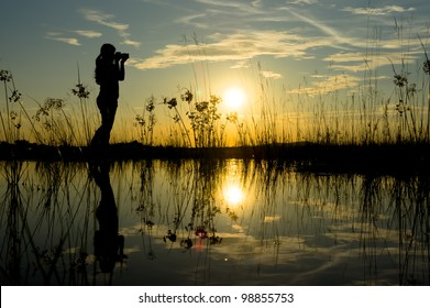 Silhouette of young woman photographer during sunset