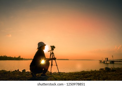 silhouette of young woman photographer,  of landscape at sunset.