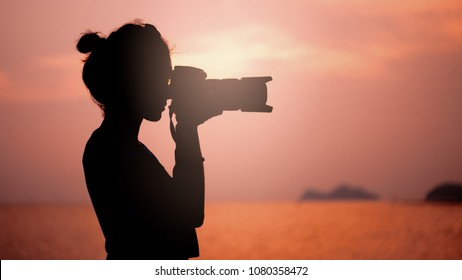 silhouette of young woman photographer, taking pictures of landscape at sunset