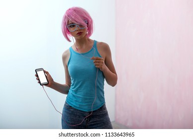 Silhouette of a young woman with a pink hair and neon glasses is holding a smartphone, with are pink headphones in her ears.