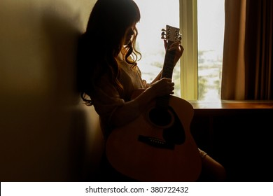 Silhouette of a young woman playing guitar alone in the dark
