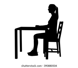 A silhouette of a young woman with a pony tail sitting on a chair at a table with her legs at a ninety degree angle underneath her.