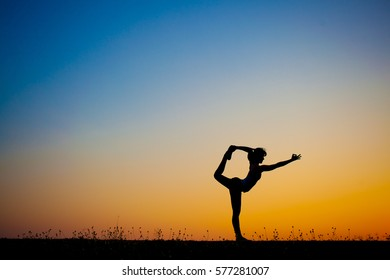 Silhouette of young woman posing doing aerial yoga  , on evening .