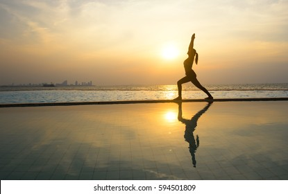 Silhouette young woman practicing pose yoga on swimming pool and the nature beach at sunset or sunrise.  Yoga and  Healthy Concept