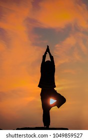 Silhouette of  young woman practicing yoga on the beach with sun flare