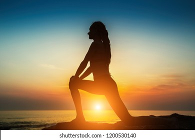 Silhouette of a young woman practicing yoga exercises on the ocean at amazing sunset.