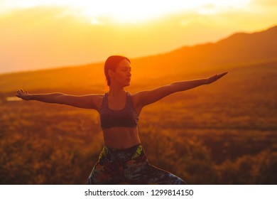 Silhouette of young woman practicing yoga or pilates at sunset or sunrise in beautiful mountain location