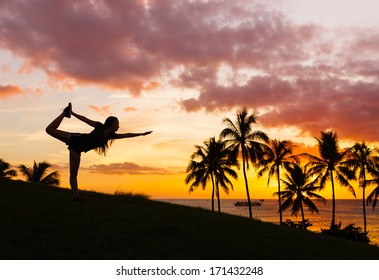Silhouette of young woman practicing yoga at sunset