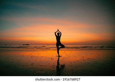 Silhouette young woman practicing yoga on the beach at amazing sunset.
