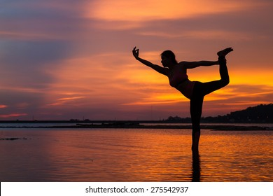 Silhouette of young woman practicing yoga on the lake at sunset.