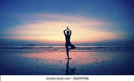 Silhouette of young woman practicing yoga on the beach at amazing sunset.