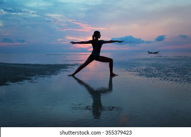Silhouette of a young woman practicing yoga on the beach at sunrise