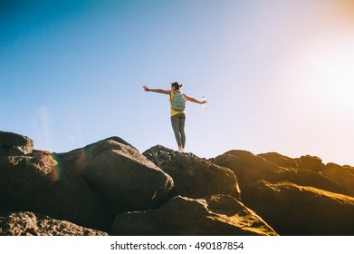 Silhouette of a young woman practicing yoga on a rocky shore