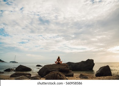 Silhouette young woman practicing yoga on the beach at sunrise in the hat. Time for peace of mind. Alone with nature. Connection with the universe.
