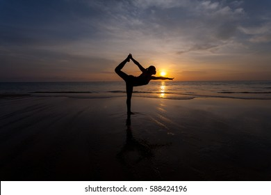 Silhouette young woman practicing yoga on the beach at sunset. For background and texture.4
