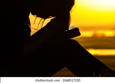 silhouette of young woman praying to God in the nature with the Bible, the girl repents of her sins, sincerely pours out feelings near the tree at sunset, the concept of religion and spirituality