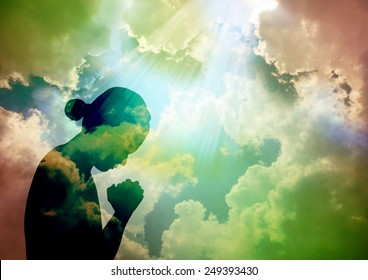 Silhouette of young woman praying to God