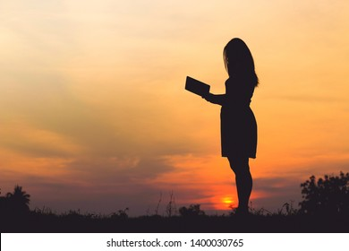 Silhouette of a young woman reading book at sunset