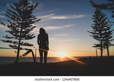 Silhouette of a young woman ready to go on the slackline in the open air between two trees at sunset at scarborough beach in Perth, Australia.