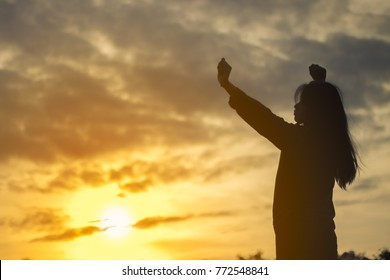 Silhouette of  young woman relaxing in summer sunset sky outdoor. People freedom style.