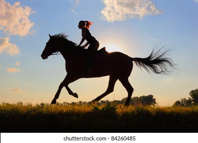 Silhouette of young woman riding her horse at dusk