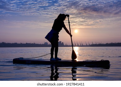 Silhouette of a young woman rowing on a SUP during a beautiful winter sunrise on the river