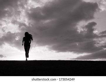 Silhouette of young woman running