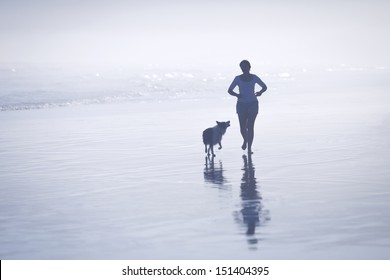 Silhouette young woman running with her dog on the beach.