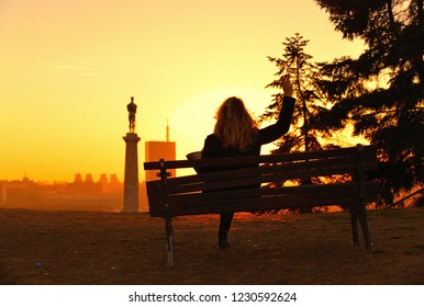 silhouette of young woman sitting on the bench at the top of park hill Kalemegdan observes the sunset on the statue of Viktor and modern buildings of New Belgrade