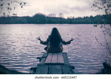 Silhouette of a young woman sitting in yoga asana - lotus posture on bank of the river