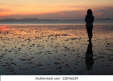 Silhouette of young woman, standing alone by the sea