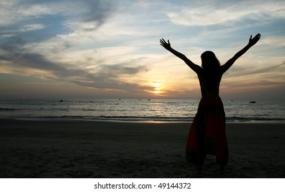 silhouette of young woman standing at the beach