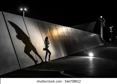 Silhouette of young woman standing next to the wall in industrial park at night. Flashlight shining on her, and there is a big shadow behind her. Barcelona, Spain