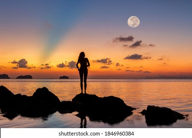 Silhouette of a young woman standing on the rocks by the sea against the backdrop of a spectacular sunset and a huge rising full moon on a summer evening