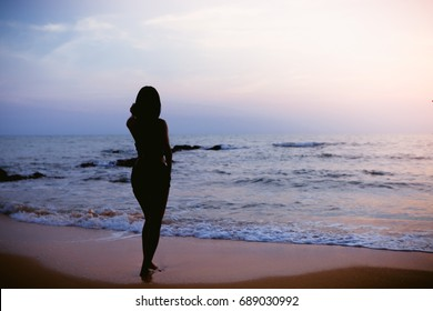 Silhouette of a young woman standing on the sand at the beach in the evening, soft focus.